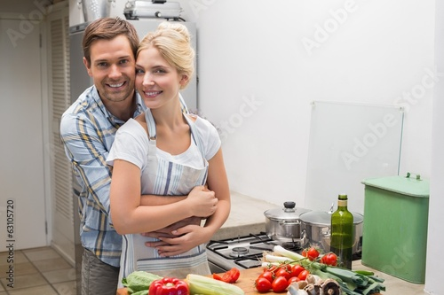Portrait of a happy couple embracing while preparing food in