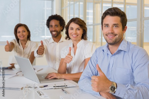 Happy business people gesturing thumbs up in meeting