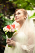 Closeup portrait of beautiful bride holding bouquet at forest