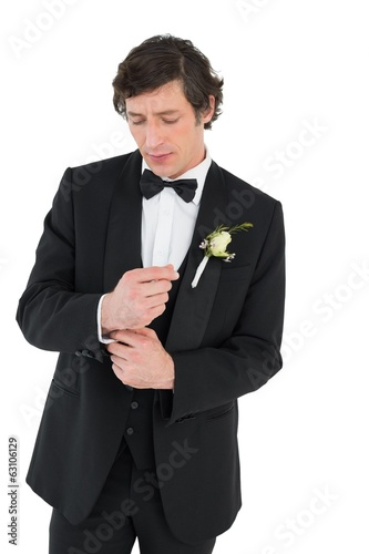 Handsome groom in tuxedo adjusting cuff link