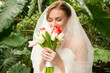Closeup portrait of beautiful bride smelling bridal bouquet