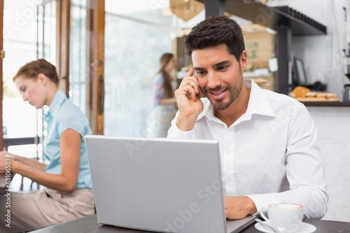 Man using laptop and mobile phone in coffee shop