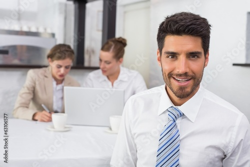 Smiling businessman with colleagues at office desk