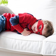 Little superhero resting on sofa
