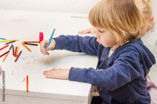 boy drawing with colorful crayons