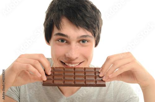 Happy man eating a yummy chocolate and having some sugar