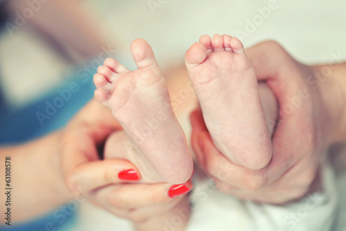 The legs of a new born in the hands of parents