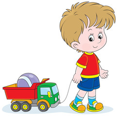 Little boy walking with a toy truck and ball