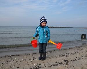 Kind mit Eimer und Schaufel am Meer