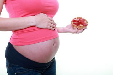 Jeune femme enceinte mangeant une tartelette aux fraises