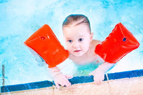 Cute toddler having fun in a swimming pool wearing red armbands
