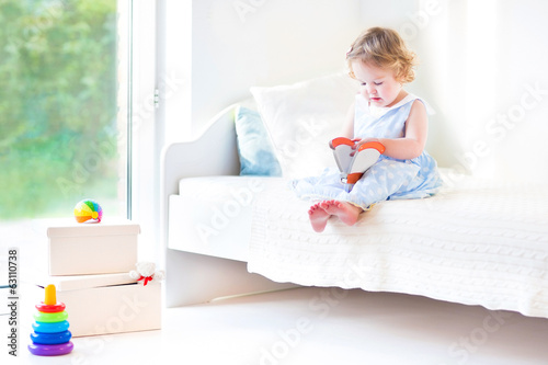 Adorable toddler girl reading a book sitting on a white bed