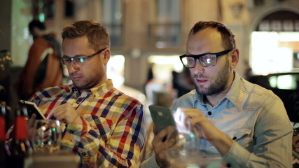 Two guys with smartphone drinking beer in the restaurant at nigh