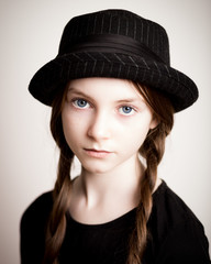 Blue eyed girl with plaits and hat