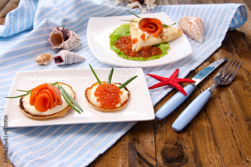 Pancakes with red caviar, salmon and mayo, green onion,