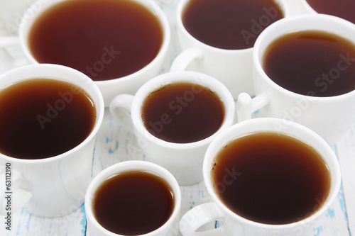 Many cups of tea on table close-up