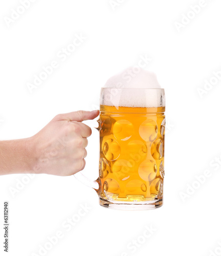 Hand holds big mug with gold beer.