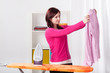 Young woman ironing shirt