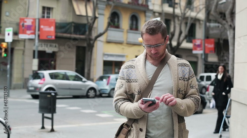 Man walking along the street and using cellphone, steadicam shot