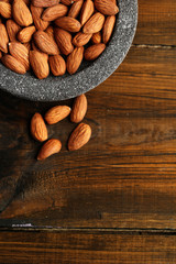 Almonds in bowl on color wooden background