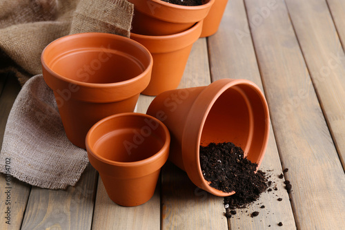 Clay flower pots and soil, on wooden table