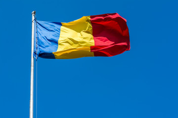Romania Flag Waving On Blue Sky