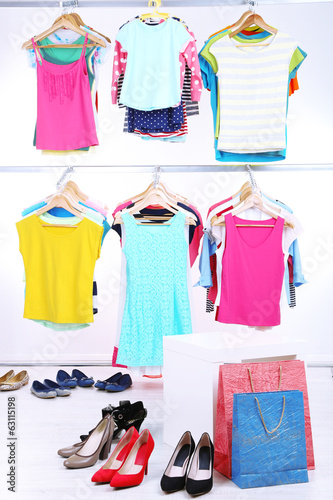 Leinwanddruck Bild Different clothes on hangers and shoes on light background
