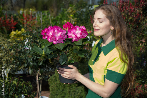 Florist smelling at blossoms of potted plan