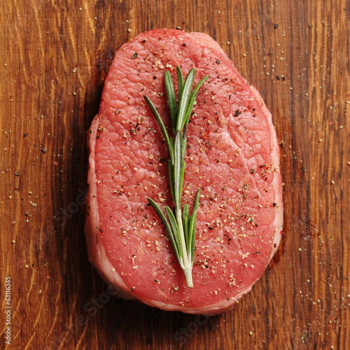 Slice of raw beef with fresh rosemary