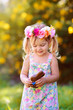 canvas print picture - cute easter child  girl eat chocolate bunny outdoor