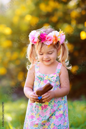 cute easter child  girl eat chocolate bunny outdoor