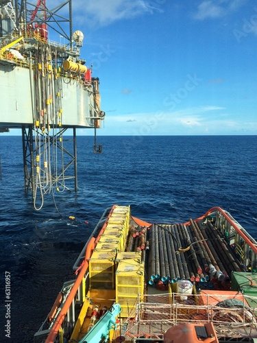 An offshore vessel during cargo loading with an oil platform