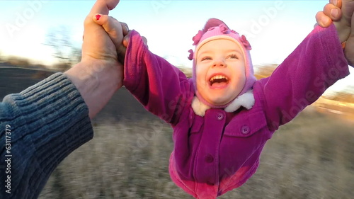 Slow Motion. Man Rotates His Little Daughter Outdoor, First Pers