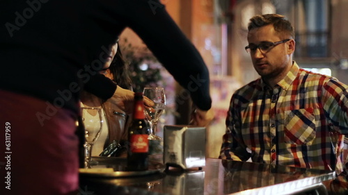 Young couple sitting in a pub at night, waiter bring beer