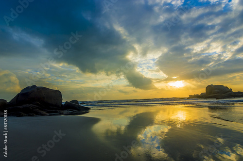 Colorful cloudy sunrise at the beach with reflection and rocks