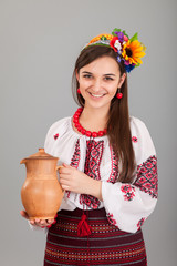 Attractive woman wears Ukrainian is holding a jug national dress