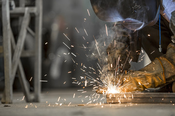 Hombre trabajando, con mascara, guantes, soldando hierro, chispa