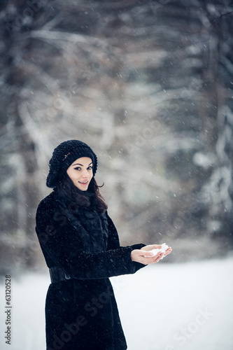 Beautiful girl standing in a snowy forest