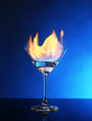 Glass with burning alcohol on blue background