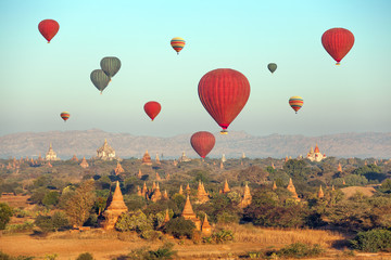 Hot air balloons over Buddhist temples at sunrise. Bagan.