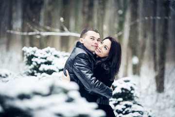 Couple in love kissing in the winter forest