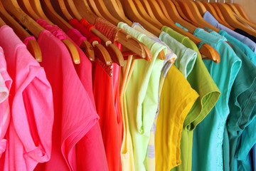 Colorful clothes on hangers in wardrobe