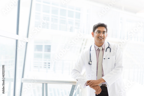 Smiling Asian Indian male medical doctor inside hospital.