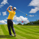 Man playing golf against blue sky with golf bag