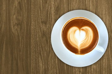 Coffee latte art on Wood background texture for design