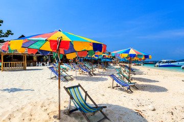 Colorful beach chairs and umbrella.