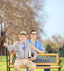 Healthcare professional and a senior posing in park