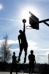 Basketball silhouette player dunking in a game