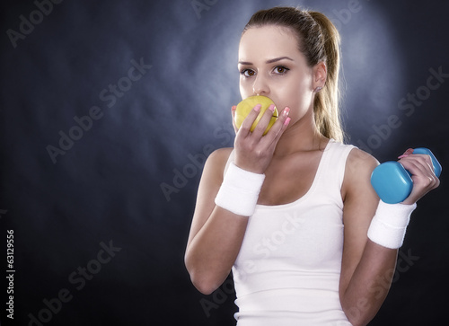 athletic woman hands ripe yellow apple, isolated on black