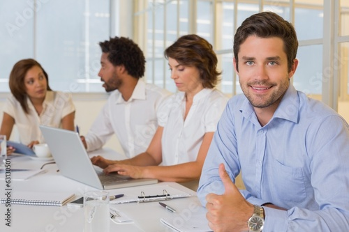 Smiling businessman gesturing thumbs up with colleagues in meeti